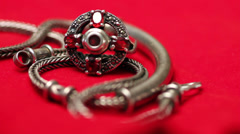 Silver ring and chain on red velvet fabric - stock footage