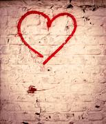 Red love heart hand drawn on brick wall grunge textured background trendy str Stock Photos