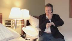Businessman using a cell phone walks in hotel room Stock Footage