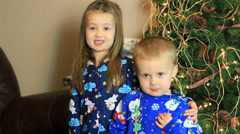 Brother and sister stand in front of Christmas tree for a picture Stock Footage