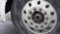Close up of lower part of a semi truck going down the road. Stock Footage