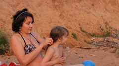 Mother brushed her hair daughter on the beach Stock Footage