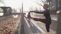 Dolly shot of beautiful runner stretching on cold autumn day Stock Footage