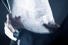 businessman with stock newspaper - stock photo
