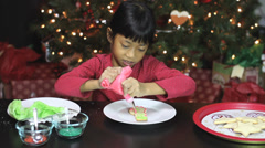Girl Adds Red Icing To Snowman Shaped Christmas Cookie Stock Footage
