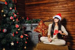 Girl with candy near christmas tree Stock Photos