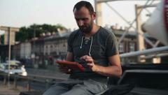 Young man using a tablet by the busy street Stock Footage