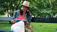 Woman reading a book and sitting on a bench in the park Stock Footage