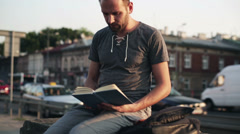 Man reading book by busy city street Stock Footage