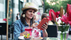 Young woman using tablet and tasting a glass of wine Stock Footage