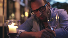 Drunk man with a glass of wine sitting in the restaurant - stock footage