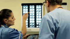 Doctors with tablet computer looking at x-ray scan of human brain HD - stock footage