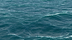 Fast fly over disturbed ocean water surface, loopable. Stock Footage