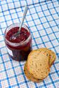 Stock Photo of bread and jar with raspberry jam on blue tablecloth