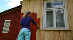 Painter girl paint rural house wood wall with paintbrush in red Stock Footage
