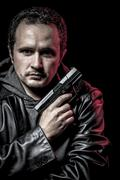 Robbery, thief, armed man with black leather jacket, dangerous Stock Photos