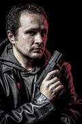 robbery, thief, armed man with black leather jacket, dangerous - stock photo