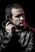 thief, armed man with black leather jacket, dangerous - stock photo