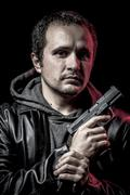 mafia, thief, armed man with black leather jacket, dangerous - stock photo
