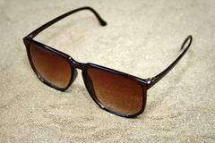 sunglasses on sand - stock photo