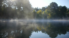 Wispy fog rising on still lake Stock Footage