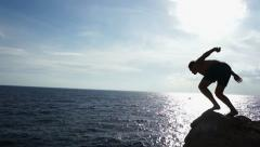 Two young men jumps from a cliff into the sea. Jumpers silhouette. HD Stock Footage