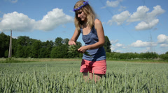 Sexy girl in pink shorts pick wheat ears in agricultural field Stock Footage