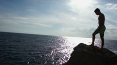Silhouette of man standing on the rock near the ocean HD Stock Footage