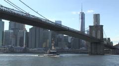 Tug sails under Brooklyn Bridge, New York city. Stock Footage