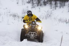 Quad bike's driver rides over snow track - stock photo