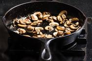 Stock Photo of sauteing sliced mushrooms in a skillet