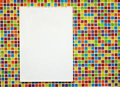 blank paper board on colorful mosaic wall - stock photo