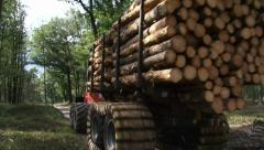 Logging forwarder drives off in forest - wide shot Stock Footage