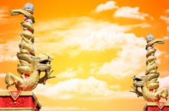 Stock Photo of dragon statue roll the column with sunset sky background