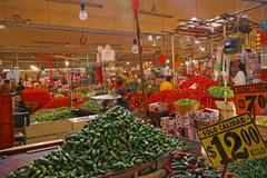 Piles of green jalapeno chili peppers and tomatoes Stock Photos