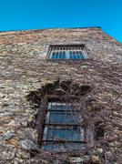 Distorted wall of an old stone building with two bar window panes and walls c Stock Photos