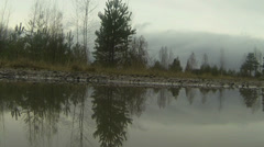 swedish forest filmed from the middle of a lake on a cloudy day - stock footage