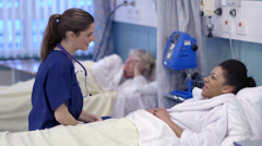 Caring nurse chats with a female patient on a hospital ward. Stock Footage