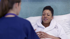 Caring nurse chats with a female patient on a hospital ward. - stock footage