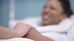 Stock Video Footage of Caring nurse chats with a female patient and holds her hand to offer comfort