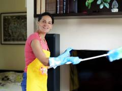 Young woman dusting tv and smiling to the camera Stock Footage