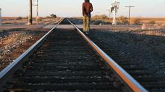 Young Man Walks Along Railroad Tracks Stock Footage