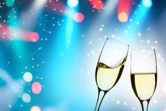 Glasses with champagne against holiday lights Stock Photos