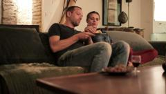 Young couple talking and eating chips on sofa at home HD Stock Footage