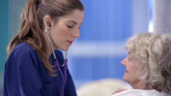 Stock Video Footage of Caring nurse chats with an elderly female patient on a hospital ward.