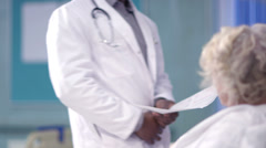 Caring doctor chats with an elderly female patient on a hospital ward. - stock footage