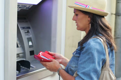 Woman taking money out of the cashpoint machine Stock Footage