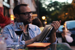 Man reading a book and drinking wine in the restaurant Stock Footage