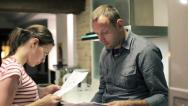 Stock Video Footage of Sad young couple reading payment bills in the kitchen HD