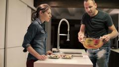 Couple taking ready, hot food from oven in the kitchen HD Stock Footage